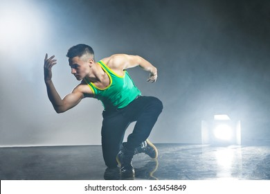 Modern style dancer posing on dark background with flashes and smoke