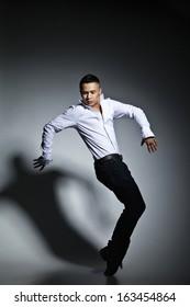 Modern style dancer posing on grey studio background