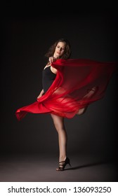 Modern style dancer with red fabric posing on a studio grey background