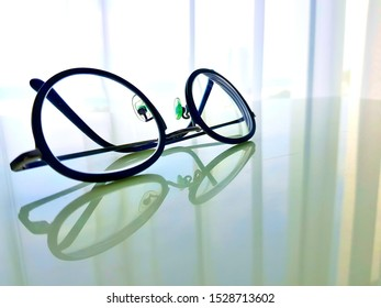 Modern style glasses placed on the clear surface table which can see the reflection and the background is the white see through curtain.