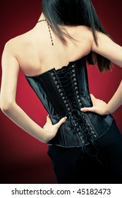 Modern style gothic woman in black leather corset on red vampire background. Hands on waist, standing back to camera.