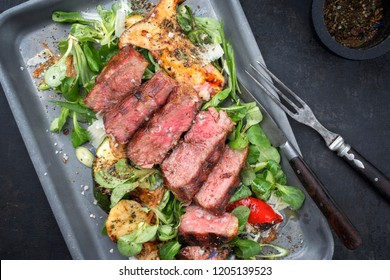 Modern Style Italian tagliata di manzo with lamb salad dry aged sliced roast beef as top view in a skillet