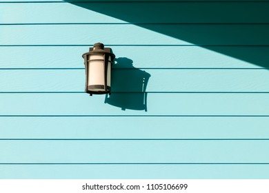 Modern style lamp on light blue wooden wall with sunlight shadow
