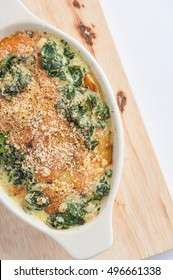 Modern style Spinach gratin (baked spinach with cheese) in ceramic bowl on wood plate