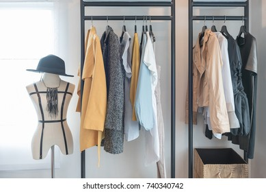 modern style wardrobe with clothes hanging on railing steel, in modern walk in closet, interior design concept
