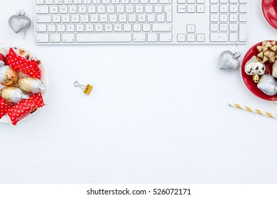 A modern styled desktop with Christmas elements in silver and white, on a pale wooden surface