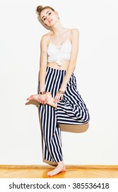 Modern styled young woman in white crochet top and white and dark blue striped long pants. Fashion model girl posing holding her leg, wearing summer boho outfit. Vertical, medium retouch.