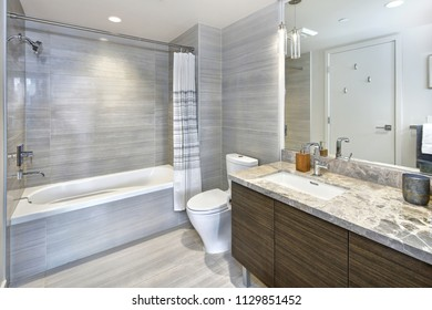 Modern and stylish bathroom design with marble vanity cabinet and gray tiling in a luxury apartment. Northwest, USA