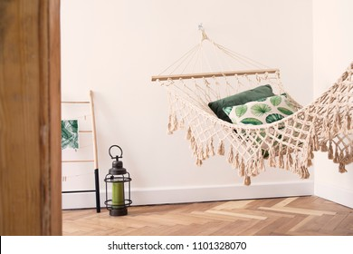 Modern and stylish bedroom with natural string hammock. Bright and sunny bedroom with brown wooden parquet.