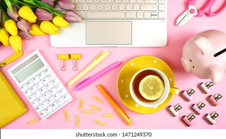 Modern stylish business and finance desk workspace coffee break with high tech touchscreen laptop and pink and yellow theme accessories.