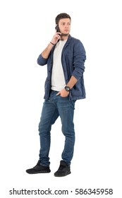 Modern stylish casual man talk on the mobile phone looking back over shoulder. Full body length portrait isolated over white background.