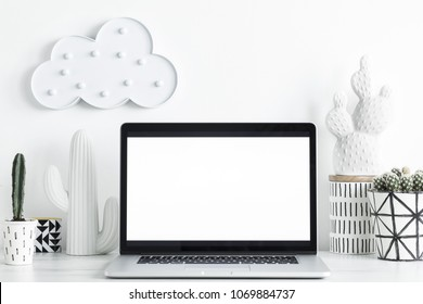 Modern and stylish desk with a cacti, cloud and  laptop with white screen. Workplace of creative designer.