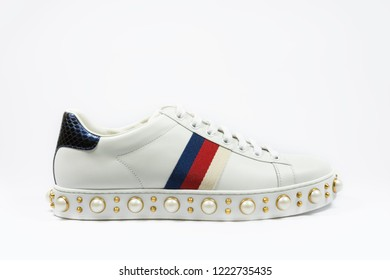 Modern, stylish, fashionable sneaker with red navy blue stripes and pearls decoration on an white background. Fashion concept.