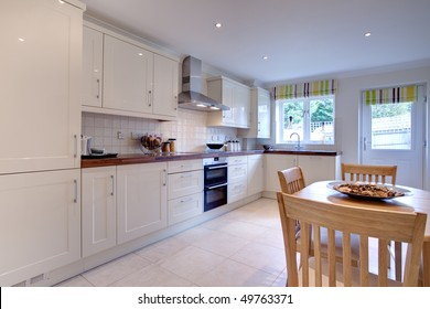 modern stylish kitchen with fitted appliances, table and chairs