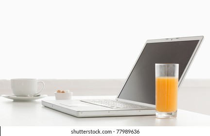 Modern and stylish laptop on a table while breakfast time in the kitchen