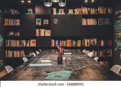 Modern stylish library with black furniture and variety of books