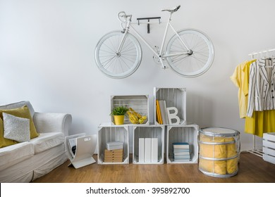 Modern stylish lounge with shelf of wooden boxes. White vintage bicycle hanging on wall