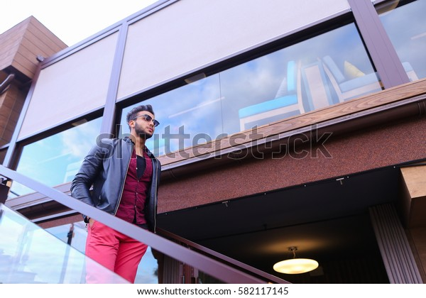 Modern stylish man, students gathered to spend time at restaurant and decided to have dinner, arranged meeting with girl and is waiting for her at entrance to restaurant, poses for catalog of men's