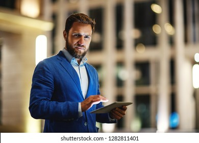 Modern stylish man in suit holding tablet and looking seriously at camera on blurred background of night buildings in lights