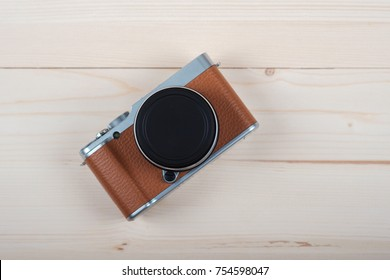 modern and stylish mirrorless camera brown color on a light wooden Board