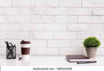 Modern and stylish office desktop with coffee to go and supplies in front of white bricks wall, copy space