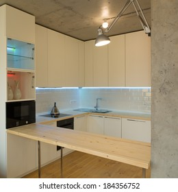 Modern and stylish white kitchen. Concrete ceiling. Wooden floor and countertop