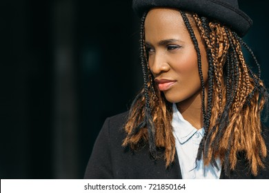 Modern stylish youth. Pretty black female. Young African American woman closeup, dark background with free space, beauty concept