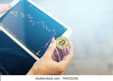 modern successful girl holds a gold bitcoin and a tablet with charts of crypto currency