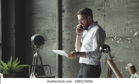 Modern successful man speaks positively on the phone, smiling standing in front of a large panoramic window. Designers discusses the color palette (pantone) with the customer. Office in loft style.
