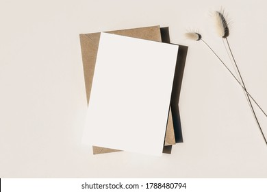 Modern summer stationery still life. Lagurus ovatus grassy foliage, craft envelope and long shadows. Blank greeting card mock up scene. Beige table background in sunlight. Flat lay, top view. - Shutterstock ID 1788480794
