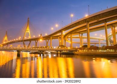 Modern Suspension bridge and highway curved riverside at twilight scene with golden light