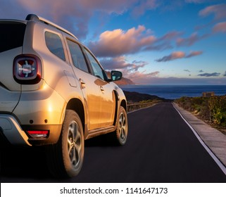 modern SUV speeding at high speed on the way leading to the ocean