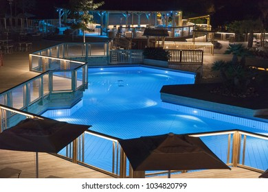 Modern swimming pool with railing at night