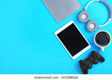 Modern tablet computer with joypad, headphones and cup of coffee on color background