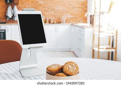 Modern tablet computer on holder in kitchen