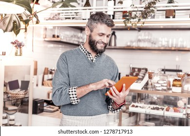 Modern tablet. Delighted positive man using his tablet while searching for the information on the Internet