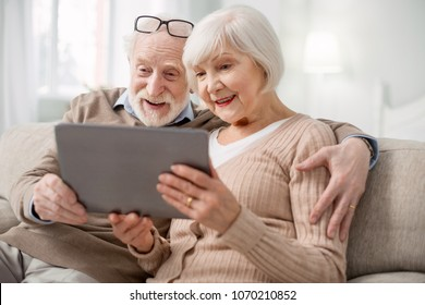 Modern tablet. Nice pleasant senior couple sitting together on the sofa while using modern tablet