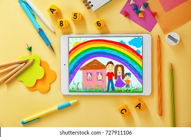 Modern tablet and school stationery on color background. Children's drawing on screen