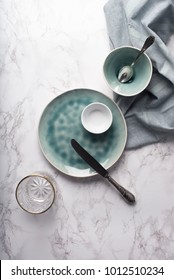 Modern tableware from above. Empty glass, plate and bowls with napkin on marble counter. Copy space.