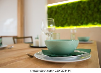 Modern tableware with ceramic bowl and plates on the wooden table
