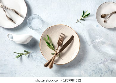 Modern tableware, overhead flat lay shot with olive branches. Mediterranean cuisine restaurant concept. Trendy plates and glasses, top view