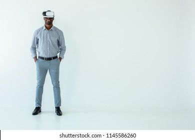 Modern tech in use. Full length of cheerful afro american man wearing VR glasses and smiling against white background