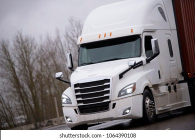 Modern technically equipped with innovations white big rig long haul semi truck tractor transporting container with commercial cargo on flat bed trailer on wet dangerous road in rainy storm weather