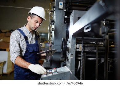 Modern technician with touchpad consulting online recommendations about repairing industrial machines