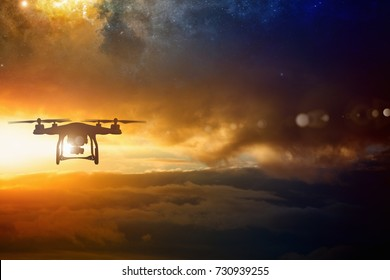 Modern technological background - silhouette of flying drone in glowing red sunset sky. Elements of this image furnished by NASA