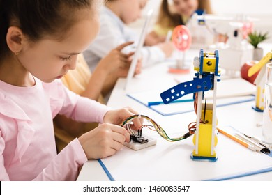 Modern technologies. Girl building robot, working with wires in class