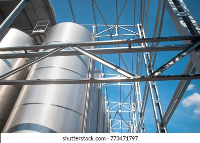 Modern  storage technology agro-industry, metal containers for grain business  granary trail perspective . Grain-drying Complex, Commercial  Seed Silos in Summer , sunny day, blue sky, white clouds .