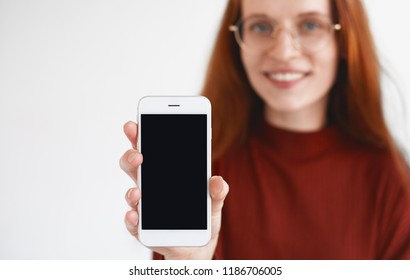 Modern technology and communication concept. Adorable redhead woman showing her new electronic device and smiling, holding cell phone with blank copyspace screen for your content. Film effect