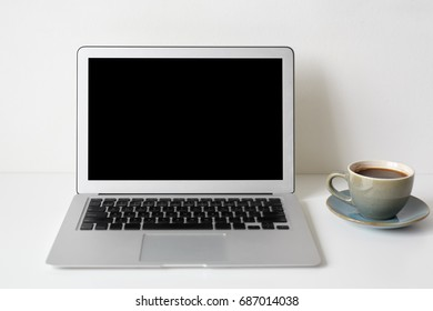 Modern technology, communication, electronic devices, gadgets, work and communication. Mock up of workplace: white table with coffee cup and generic notebook computer with blank copyspace screen