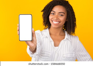 Modern Technology Concept. African american woman showing blank phone screen, mockup, selective focus